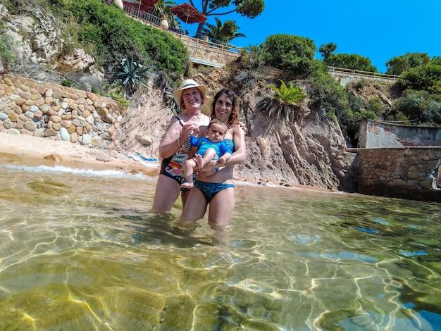 지중해의 코스타 브라바(costa brava), 지로나(girona)의 토사 데 마르(tossa de mar) 마을 옆에 있는 칼라 카니예(cala canyet)에서 여름을 즐기는 할머니, 어머니, 아들