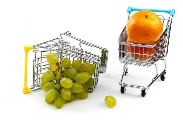 白い背景で隔離のショッピングカートのブドウ。ショッピングカートで熟したおいしい緑のブドウ。ブドウ取引の概念。オンラインショッピングの概念。カートと白い背景の上のブドウ。
