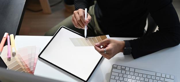 그래픽 디자이너가 직장에서 색상 선택 및 디지털 태블릿 작업을하고 있습니다.