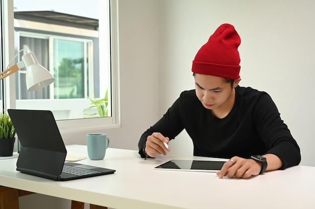 Графический дизайнер или фотограф в красной шерстяной шляпе в руке держит рисунок стилусом на дигитайзере.