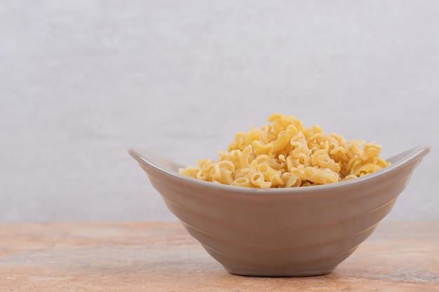 대리석 배경에 준비되지 않은 마카로니의 회색 그릇. 고품질 사진