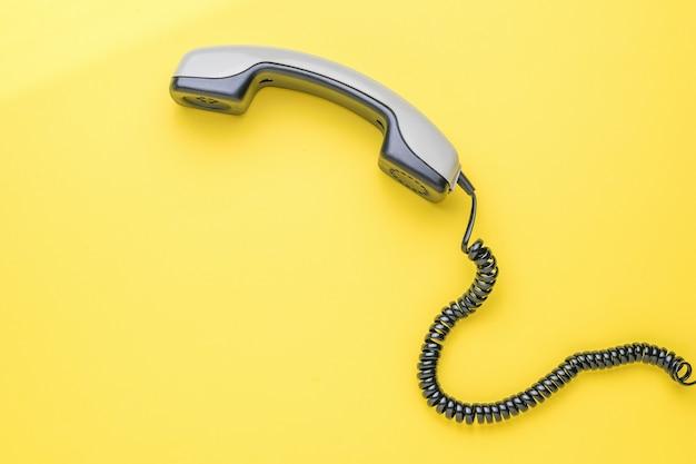 黄色の背景に黒い電話線が付いた灰色の携帯電話。フラットレイ。