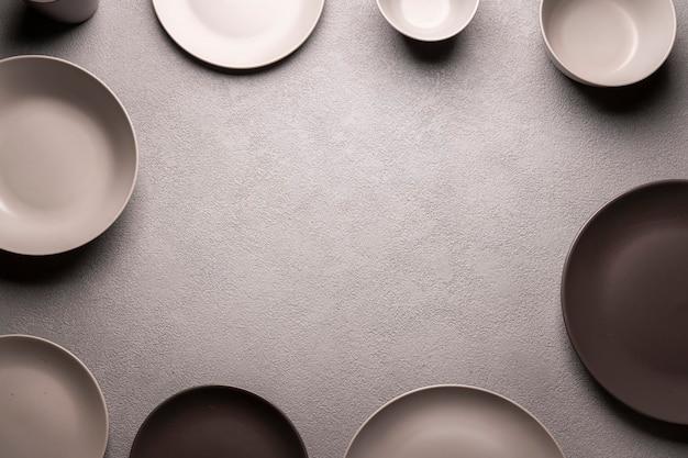 Серый кухонный обеденный стол в обрамлении тарелок и мисок. концепция меню для ресторана или приглашения. пустое место для текста макета copyspace.