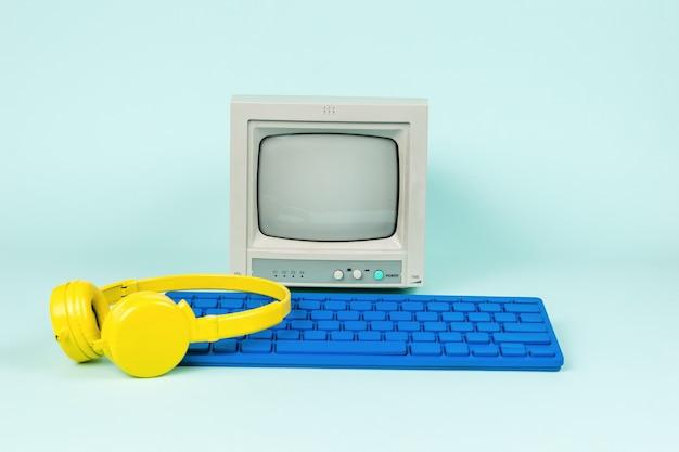 파란색 배경에 회색 모니터, 파란색 키보드 및 노란색 헤드폰.