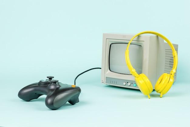 灰色のモニター、ゲーム機、水色の背景に黄色のヘッドフォン。
