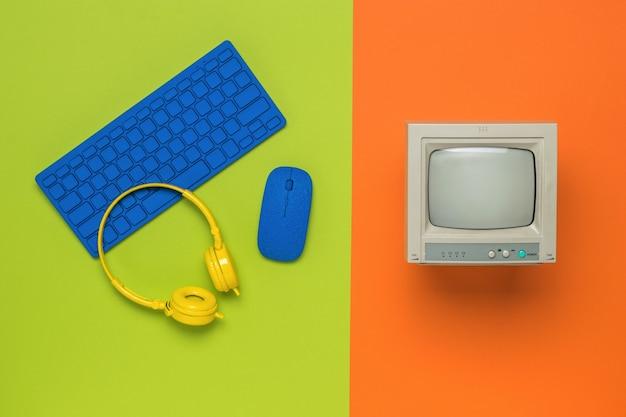 オレンジ色の背景に灰色のモニター、緑色の背景にコンピューターアクセサリ。フラットレイ。