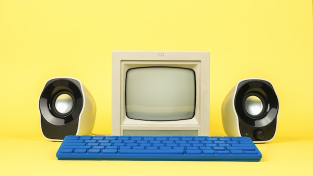 スタイリッシュなスピーカーと黄色の背景に青いキーボードを備えた灰色のモニター。スタイリッシュなヴィンテージ装備。