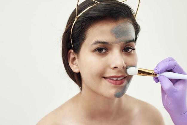 素敵な若い女性に灰色の泥マスクを適用します。美容師の手順。