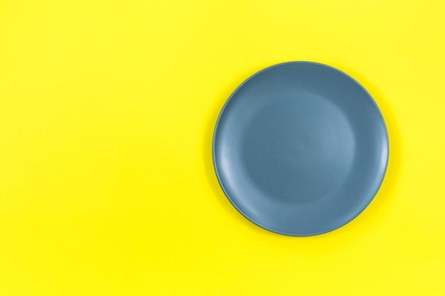 Серая тарелка на ярко-желтой поверхности