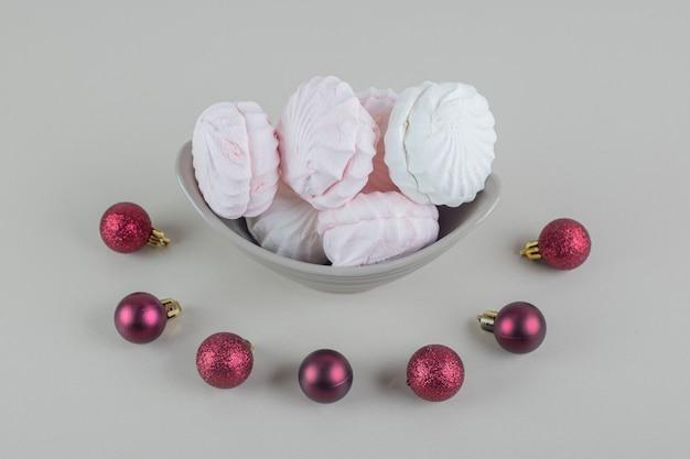 Серая тарелка с ванилью и розовыми зефирами с елочными шарами.