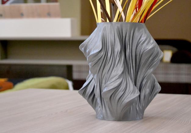 3d 프린터로 인쇄된 회색 꽃병은 내부 클로즈업 테이블에 서 있습니다