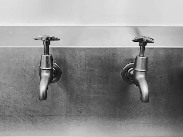 Снимок напольных смесителей на стене в оттенках серого.
