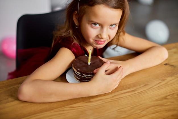 Жадная маленькая девочка в шляпе на день рождения держится на именинном торте, корчит рожи