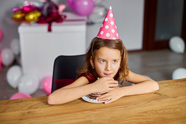욕심 많은 소녀가 생일 케이크를 들고 생일 모자를 쓰고있다