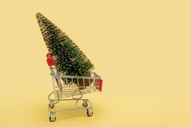 スーパーマーケットのカートにある緑のクリスマスツリー。