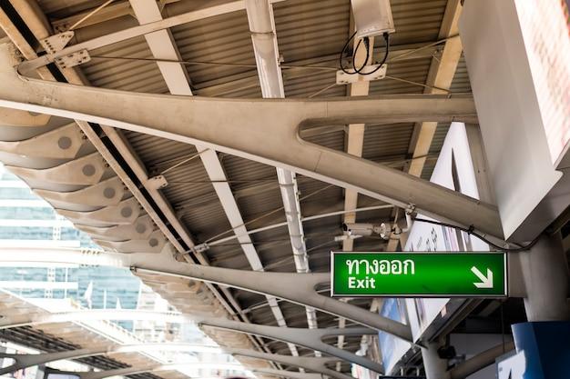 지붕 근처 벽에 설치된 녹색 출구 표지판.