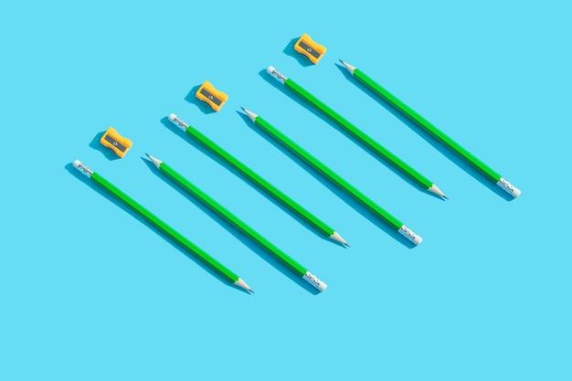 Зеленый графитовый карандаш с ластиком и оранжевой точилкой лежит на синем плоском слое.