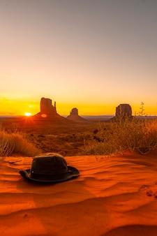 ユタ州モニュメントバレーの夜明けの赤い砂の上の緑の帽子。縦の写真