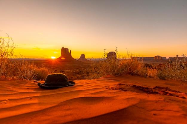 ユタ州モニュメントバレーの夜明けの赤い砂の上の緑の帽子
