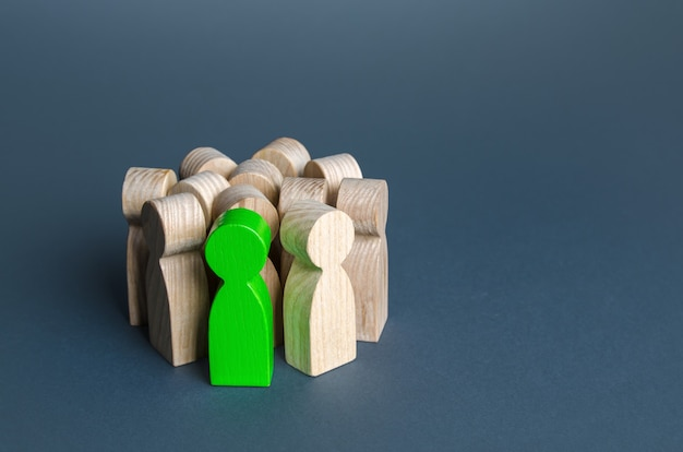 녹색 남자는 사람을 찾는 재능있는 후보자를 모집하는 사람들의 군중에 서 있습니다