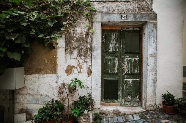 Зеленая старая дверь на одной из старых улиц района алфама
