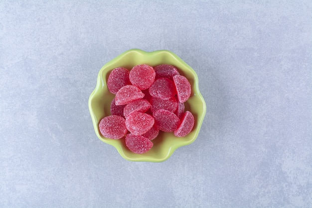灰色の表面に甘いゼリーキャンディーでいっぱいの緑色のプレート
