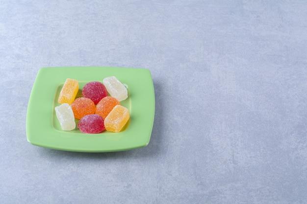 회색 표면에 달콤한 젤리 사탕으로 가득 찬 녹색 접시