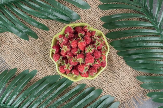 Зеленая тарелка, полная вкусной малины на вретище. фото высокого качества