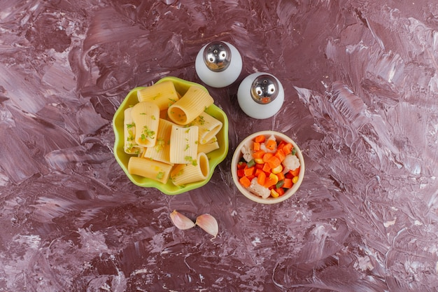 Зеленая тарелка сухих сырых макарон с салатом из свежих овощей и специями.