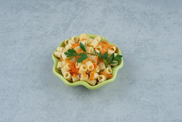 Зеленая тарелка макарон и брокколи на белом фоне. фото высокого качества