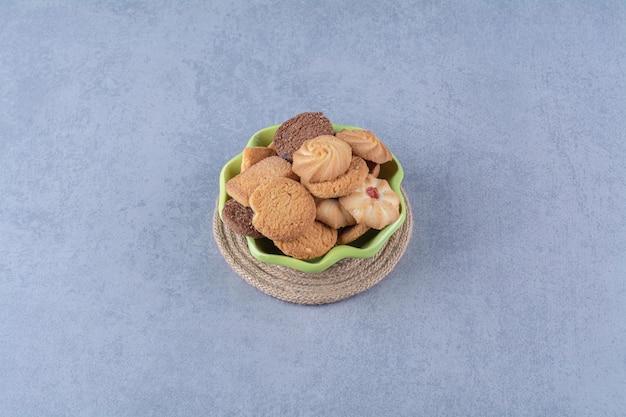 荒布の上に甘い丸いおいしいクッキーが付いた緑のプレート