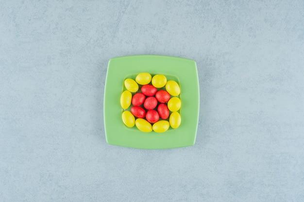 白い背景の上の甘い黄色と赤のキャンディーと緑のプレート。高品質の写真