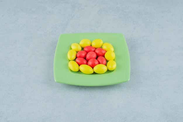 白い表面に甘い黄色と赤のキャンディーと緑のプレート