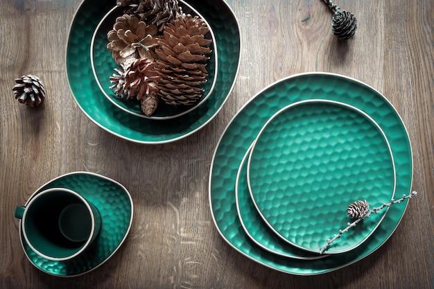 녹색 접시 세트:나무 배경에 찻잔, 접시, 접시, 다양한 콘. 크리스마스 테이블 장식, 마법의 휴일. 평면도.