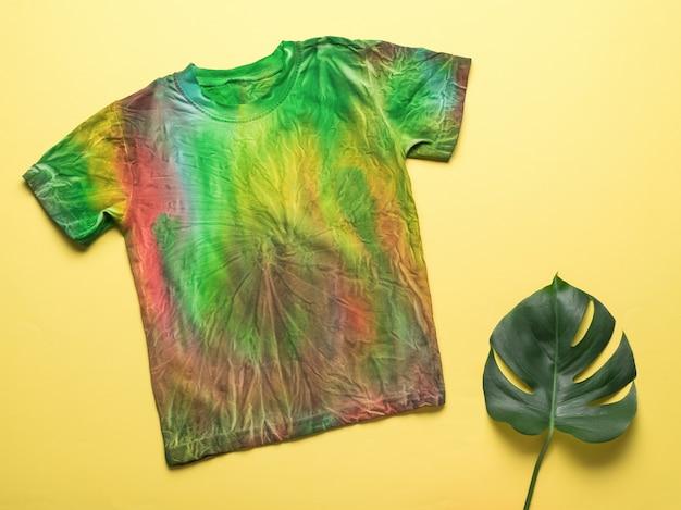 노란색 바탕에 녹색 넥타이 염료 티셔츠와 몬스테라 잎. 집에서 손으로 옷을 색칠합니다. 플랫 레이.