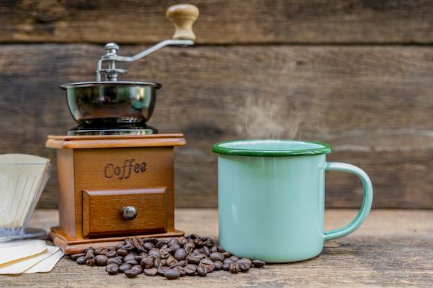 木製のテーブルにコーヒーグラインダーとコーヒー豆とホットコーヒーの緑の錫カップ。