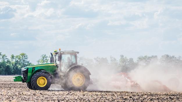 녹색 트랙터가 현장에서 일하고 있습니다. 토양 재배. 농업 작업.
