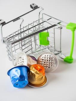 食料品のバスケットは、白い背景の上に配置されます。使用済みのアルミ製コーヒーカプセルがこぼれました。エコロジーと製品の再利用の概念