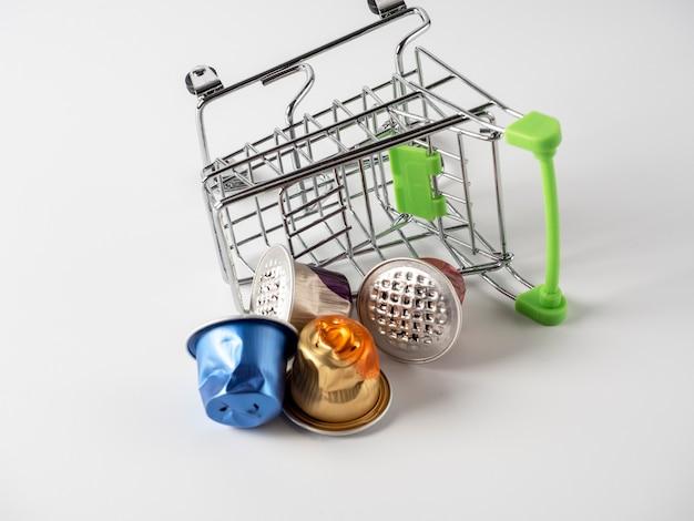 食料品のバスケットは、白い背景の上に配置されます。使用済みのアルミコーヒーカプセルがこぼれました。
