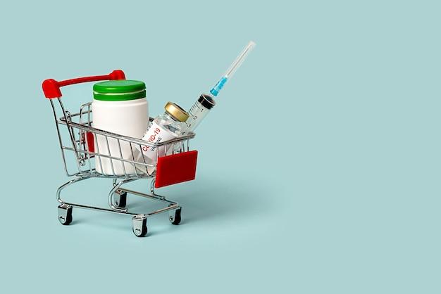 의료 용품이 담긴 식료품 바구니. 바이러스에 대한 주사기와 백신. 파란색 배경에.