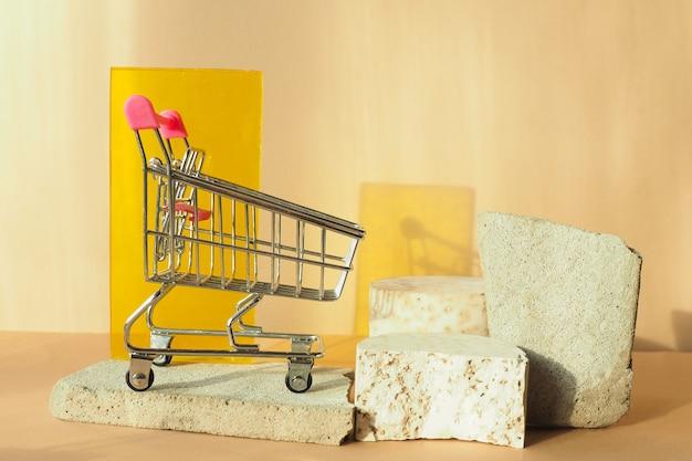 コンクリートスラブの食料品カート、コンクリートの表彰台、ベージュの背景に黄色のプレキシガラス。