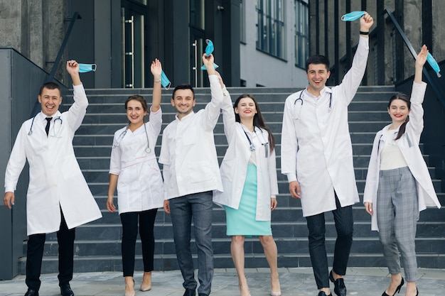 コロナウイルスパンデミックcovid-19の最中に医師グループが顔から保護マスクを脱いで笑っています。コロナウイルスとヘルスケアの概念。