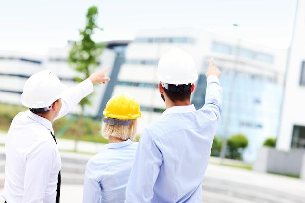 Группа архитекторов на месте указывает на современные здания