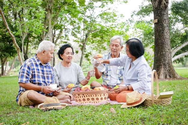 アジアの長老たちのグループが、日陰の庭で座ってリラックスし、軽食を準備しています。彼らが幸せになるのを見てください。高齢者コミュニティの概念。公園でのピクニック