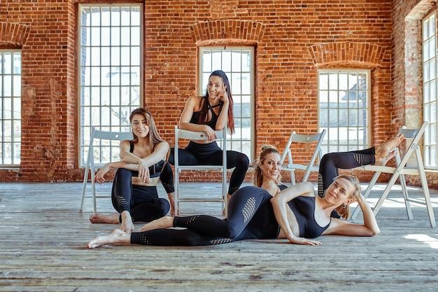 아름다운 스포츠 소녀 그룹이 카메라 스튜디오에서 포즈를 취하고 있습니다. 의자에 앉아 재미 있고 쉽게 피곤합니다. 팀워크, 피트니스 개념, 스포츠 배너, 복사 공간.