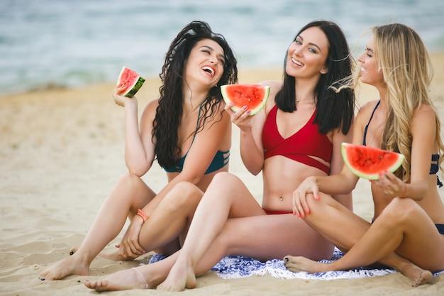 Группа красивых молодых девушек на пляже загорает