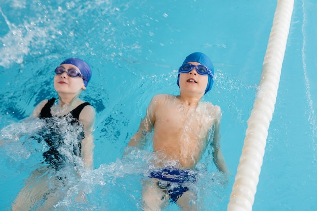 男の子と女の子のグループがトレーニングを行い、インストラクターと一緒にプールで泳ぐことを学びます。子供のスポーツの発展。