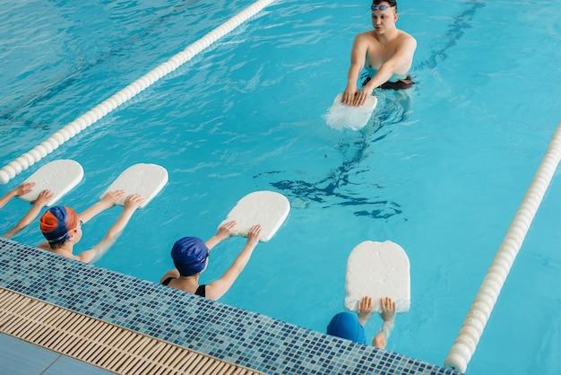 한 무리의 소년 소녀들이 강사와 함께 수영장에서 훈련하고 수영하는 법을 배웁니다. 어린이 스포츠의 발전.