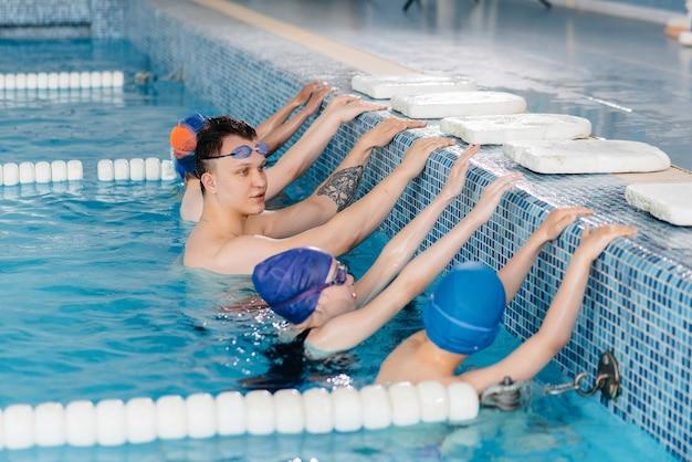 Группа мальчиков и девочек тренируется и учится плаванию в бассейне с инструктором. развитие детского спорта.
