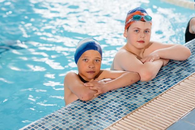 소년 소녀 그룹이 강사와 함께 수영장에서 수영을 배우고 훈련합니다.